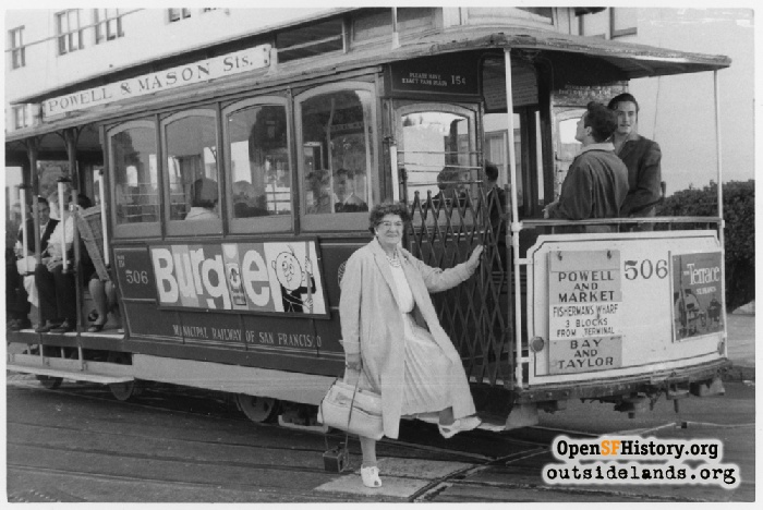 Older woman posing with cable car #506 at Bay and Taylor turntable, 1962.