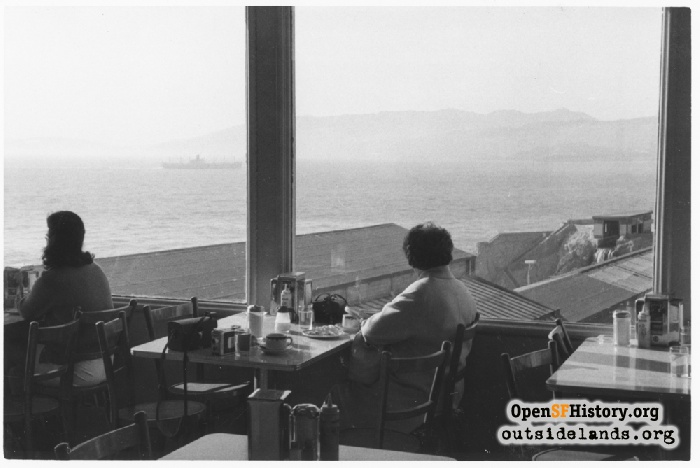 Older woman sitting at table alone at Cliff Chalet, view of Sutro Baths through window, 1962.