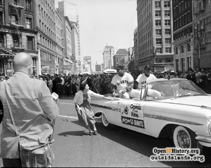 Orlando Cepeda and Felipe Alou greet fan from car at Montgomery and Market during San Francisco Giants Welcome Parade, April 13, 1959.