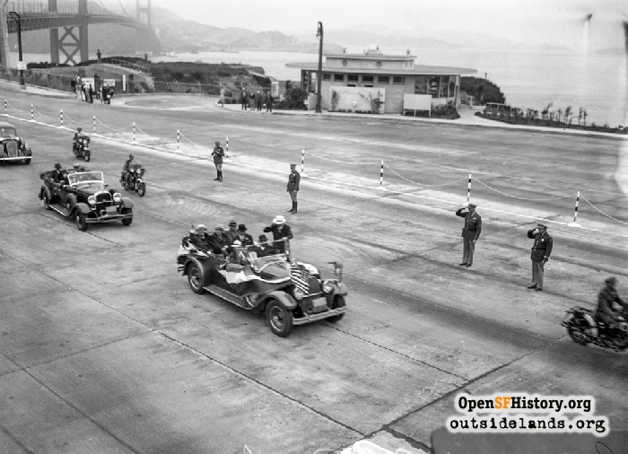 President Franklin Roosevelt approaching toll plaza in motorcade after crossing Golden Gate Bridge. Round House restaurant in background.