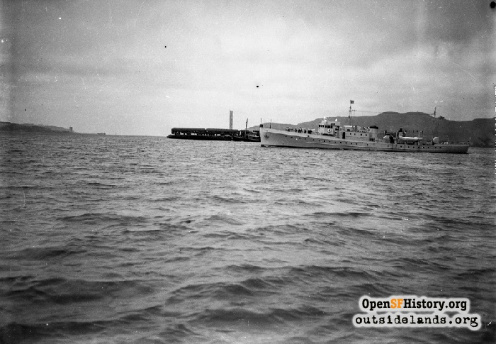 Prisoners being transported from Tiburon to Alcatraz in train on barge. Coast Guard Cutter Daphne, WPC-106, in foreground. August 22, 1934.