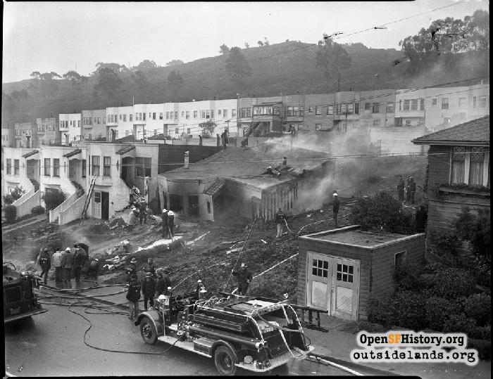 View to southeast and San Bruno Mountain. 73 Alexander Avenue collapsed and on fire. December 5, 1943.