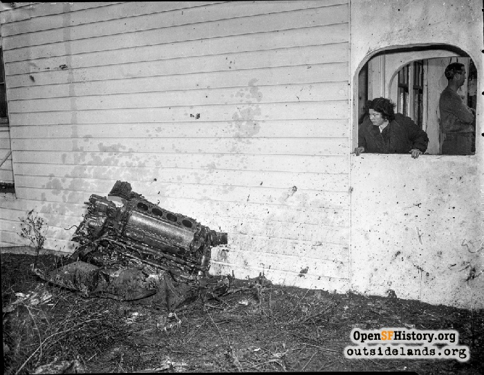 Mrs. Ralph Carboni at 52 Alexander Avenue looking at the plane engine that had thudded against her living room wall on December 5, 1943.