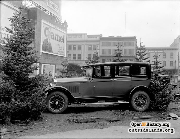 Automobile parked in Christmas tree lot on Market Street, circa 1925.
