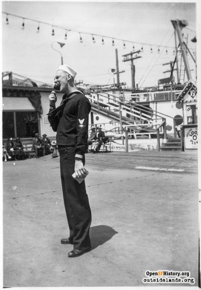 Sailor eating a candy apple on Midway at Playland, circa 1937.