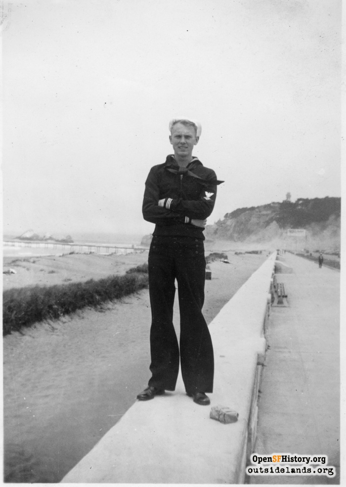Sailor standing on Great Highway Esplanada seawall with Lurline Pier, Seal Rocks, and Cliff House behind him, circa 1937.