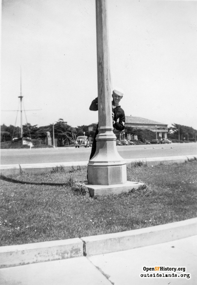 Sailor posing behind light pole on Great Highway Esplanade across from Gjoa and Beach Chalet, circa 1937.
