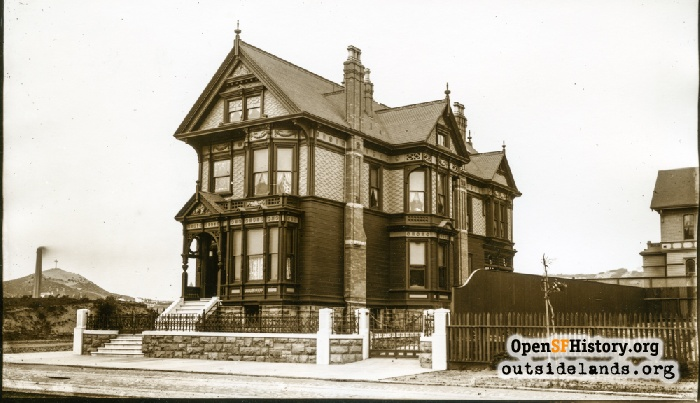 The Heywood home at 1490 Hayes at Baker Street showing Lone Mountain and the McAllister cable car powerhouse in the background, 1890.