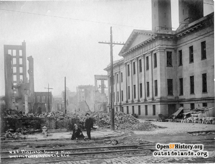 View north to men sitting on Mission St., holding champagne bottles amid earthquake ruins behind the U.S. Mint.