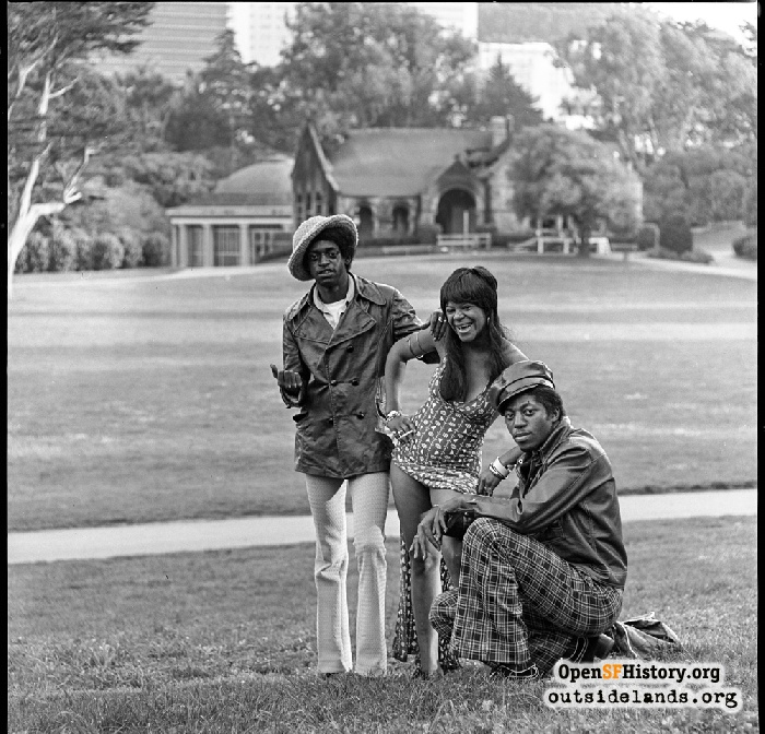 Three very stylishly dressed individuals on Hippie Hill in Golden Gate Park. Fire damage to Sharon Building in background, 1974.