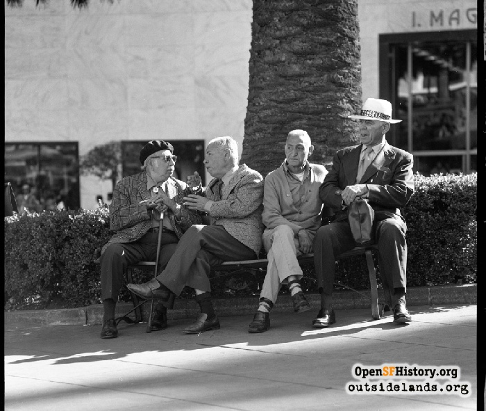 Four men on bench in Union Square. I. Magnin department store behind, October 1973.