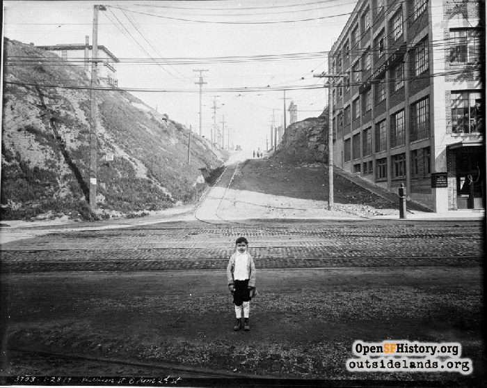 Boy with influenza mask pulled down at intersection of Harrison and 2nd Street, January 28, 1919.
