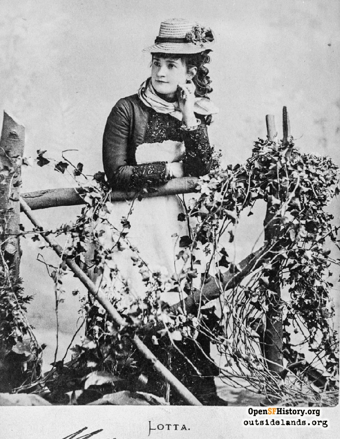 Studio portrait of Lotta Crabtree with prop ivy-covered fence, 1870s.