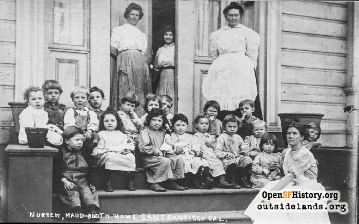 Small children pose with staff on steps of Maud B. Booth Home for Children at 812 Shotwell Street, 1910s.
