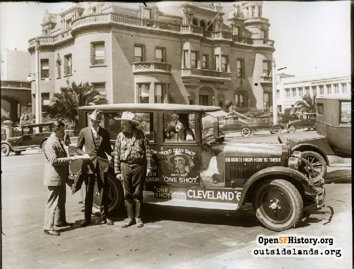 Traveling lecturer Col. King Stanley and his wife Grace Raymond Stanley (in car) during a promotional journey for Chandler-Cleveland Motor Car Co. Claus Spreckels mansion in background. Van Ness Avenue near Clay Street, September 1924.