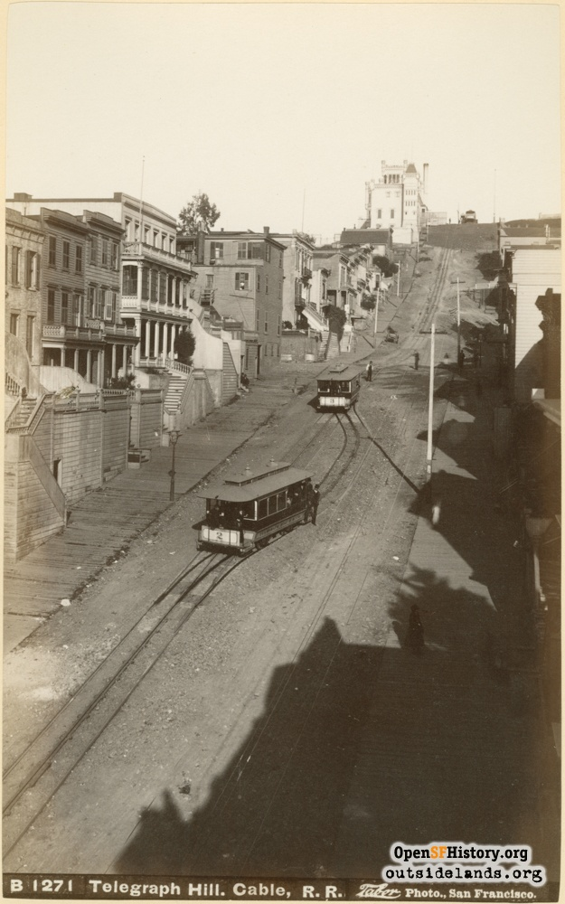 View up Greenwich Street from near Stockton Street. Two Telegraph Hill Railroad funicular cars enter passing track. Layman's German Castle at top of hill.