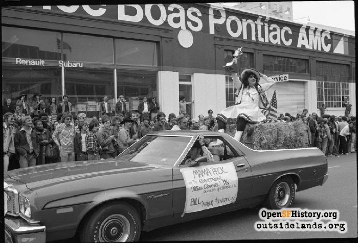 Miss Cowgirl 74/75 on hay bale in back of car at O'Farrell and Polk during Gay Freedom Day Parade, June 30, 1974.